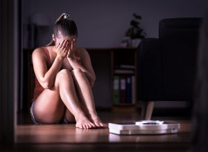 Woman having stress about weight loss, diet or gaining weight. Eating disorder, anorexia or bulimia concept. Young girl crying and sitting on the floor with scale. Underweight person sad about obesity