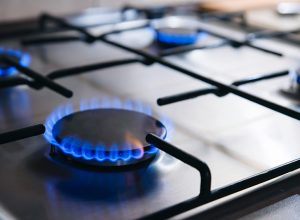 Gas kitchen stove cook with blue flames burning. Panel from steel with a gas