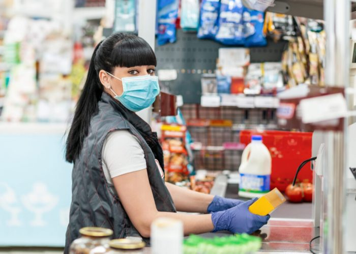 A young woman in a medical mask and gloves, working at the checkout in a supermarket. Concept of coronovirus, protection from infection and industrial crisis.