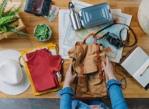 Top view of young woman packing backpack for vacation trip holiday, desktop travel concept.