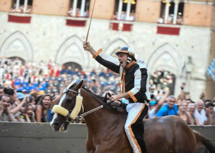 """Jockey of the the contrada """"Lupa"""" Giuseppe Zedde, known as """"Gingillo"""", rides his horse Portgo Alabe as they compete and win the historical Italian horse race Palio di Siena , on August 16, 2018, in Siena. (Photo by Carlo BRESSAN / AFP)"""